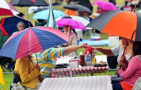Thursday's Picnic Pops crowd at Cannonsburg Ski Area deal with some rain early on. (Dave Raczkowski | The Grand Rapids Press)